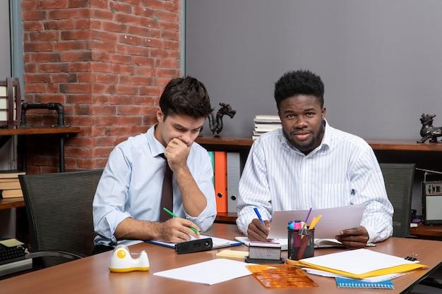Vooraanzicht twee zakenpartners die zakelijke onderhandelingen voeren op kantoor