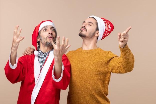 Vooraanzicht twee zelfverzekerde mannen met santahoeden die zich op beige geïsoleerde achtergrond bevinden