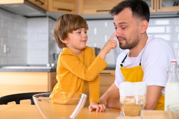 Vooraanzicht vader en kind in de keuken