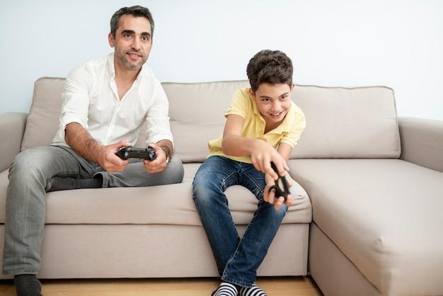 Vooraanzicht vader en kind spelen met controllers