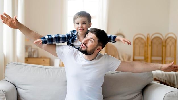 Vooraanzicht vader en kind spelen op de bank