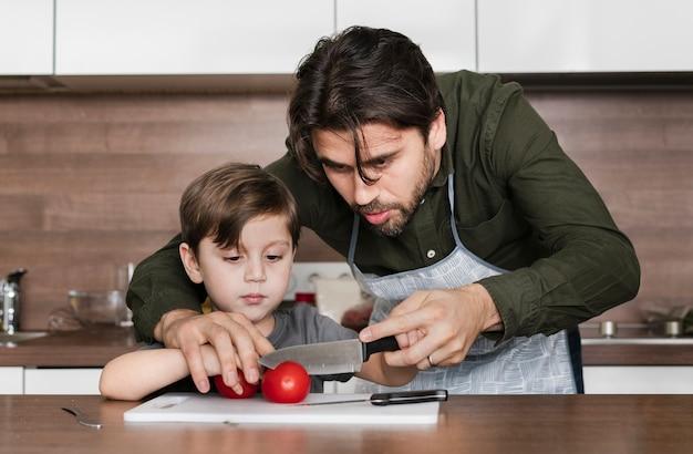 Vooraanzicht vader en zoon in keuken