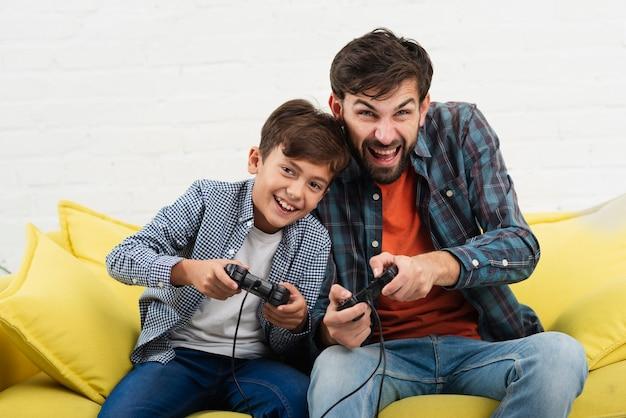 Vooraanzicht vader en zoon spelen op console