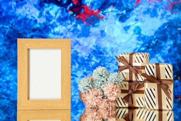 Vooraanzicht vakantiegeschenken leeg fotolijstje bloemen weerspiegeld op spiegel op blauwe cyristal achtergrond
