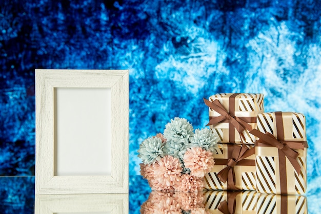 Vooraanzicht vakantiegeschenken lege fotolijst bloemen weerspiegeld op spiegel met een ijsblauwe achtergrond