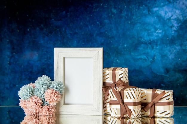 Vooraanzicht valentijnsdag geschenken bloemen wit fotolijstje weerspiegeld op spiegel op donkerblauwe achtergrond
