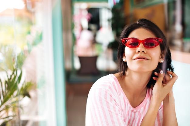 Vooraanzicht van aangenaam gebruinde vrouw in zonnebril. buiten schot van mooie brunette vrouw op achtergrond wazig.
