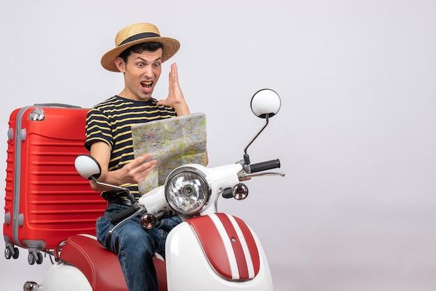 Vooraanzicht van afgevraagd jonge man met strooien hoed op bromfiets kaart kijken