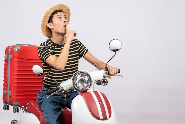 Vooraanzicht van afgevraagd jonge man met strooien hoed op bromfiets stilte teken maken