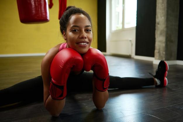 Vooraanzicht van afrikaanse atleet, vrouwelijke bokser in rode bokshandschoenen die een touw uitvoert op de vloer van een sportgymnastiek met een bokszak. martial combat art stretching, sport en wellness concept