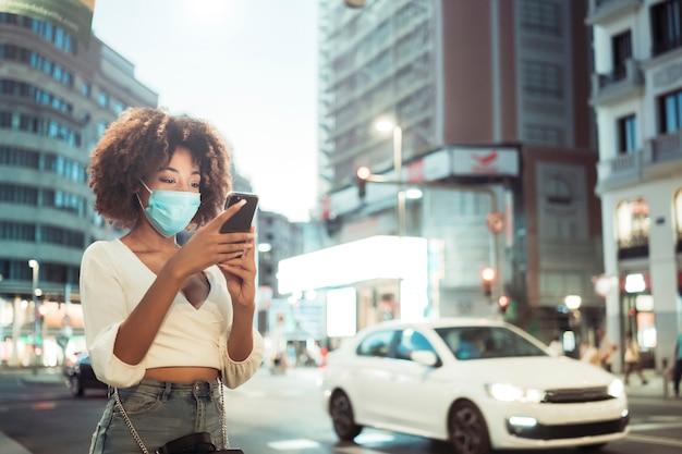 Vooraanzicht van afrovrouw met chirurgisch masker die mobiel tegen stad bij nacht gebruiken. ze draagt vrijetijdskleding. ze is in de stad.