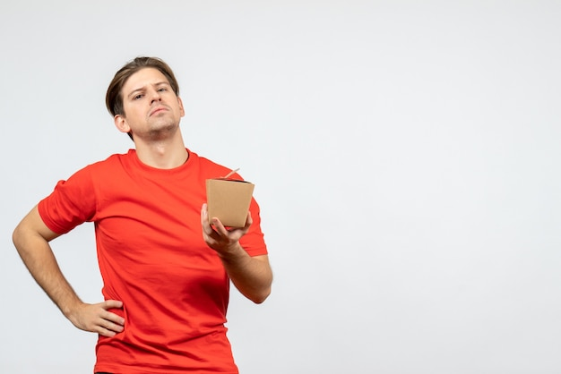 Vooraanzicht van ambitieuze jonge kerel in rode blouse die kleine doos houdt en voor camera op witte achtergrond stelt