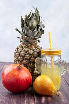 Vooraanzicht van ananassap met ananas granaatappel perzik op houten oppervlak en witte ondergrond