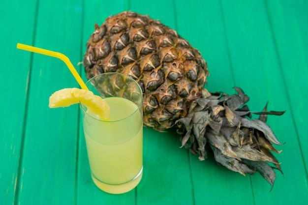 Vooraanzicht van ananassap met ananas op groene ondergrond