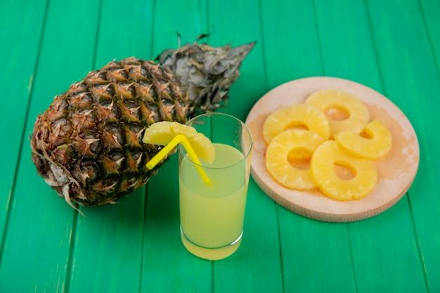 Vooraanzicht van ananassap met ananas segmenten op snijplank en ananas op groene ondergrond