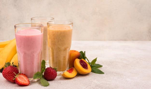 Vooraanzicht van assortiment milkshakes met fruit en kopie ruimte
