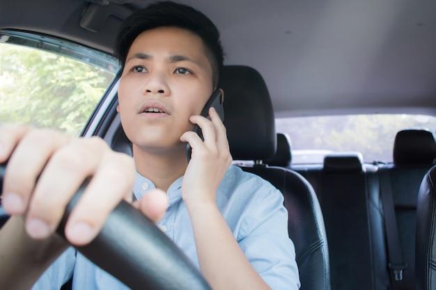 Vooraanzicht van aziatische mensen die mobiele telefoons gebruiken en gesprekken voeren tijdens het rijden.