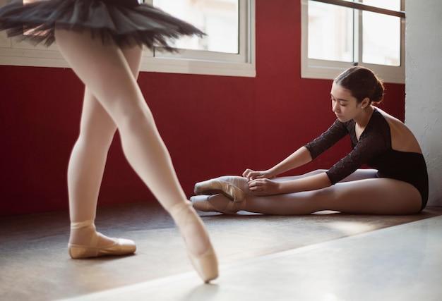 Vooraanzicht van ballerina die op de vloer repeteert