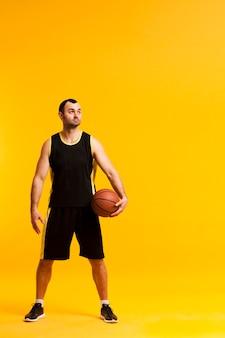 Vooraanzicht van basketbalspeler het stellen met bal dicht bij heup en exemplaarruimte