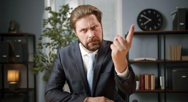 Vooraanzicht van bazige boze zakenman wijsvinger omhoog in leren teken