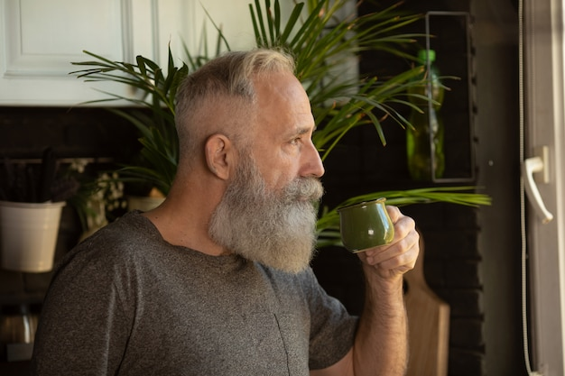 Vooraanzicht van bebaarde senior man met koffiekopje op zijn keuken