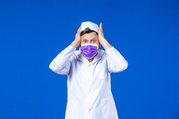 Vooraanzicht van beklemtoonde mannelijke arts in medisch kostuum en paars masker op blauw