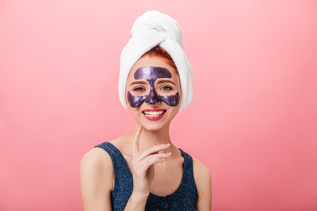 Vooraanzicht van betoverende vrouw met gezichtsmasker lachen op roze achtergrond. studio die van zalig meisje met handdoek op hoofd is ontsproten die kuuroordbehandeling doet.