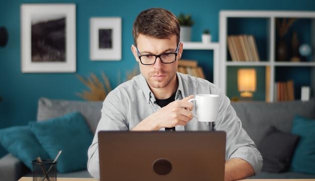 Vooraanzicht van betrokken jongeman browsen op laptop en beker zittend aan tafel in de woonkamer te houden