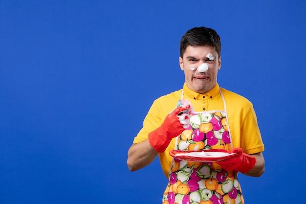 Vooraanzicht van bezorgde huishoudster met schuim op zijn gezicht wasplaat op blauwe muur