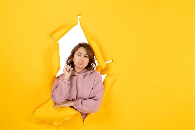 Vooraanzicht van bezorgde vrouw die diep denkt en vrije ruimte op gele gescheurde