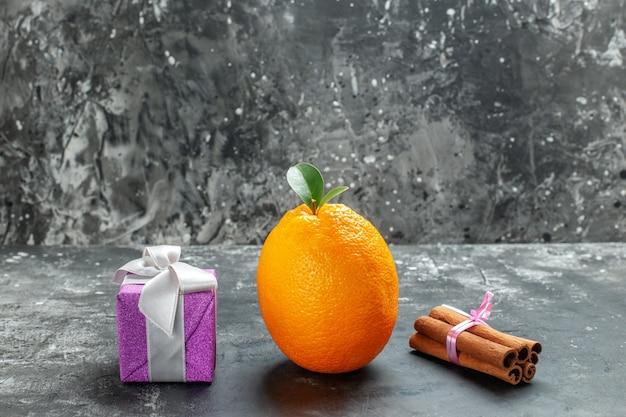 Vooraanzicht van biologische verse sinaasappel met stengel en blad in de buurt van een geschenk en kaneellimoenen op donkere achtergrond