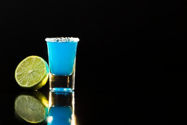 Vooraanzicht van blauwe cocktail in geschoten glas met exemplaarruimte
