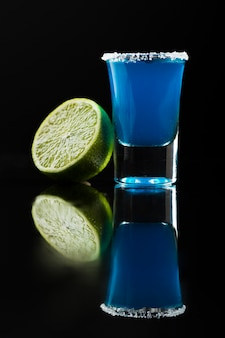 Vooraanzicht van blauwe cocktail in geschoten glas met kalk