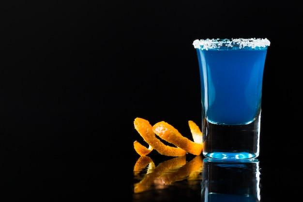 Vooraanzicht van blauwe cocktail in geschoten glas met sinaasappelschil