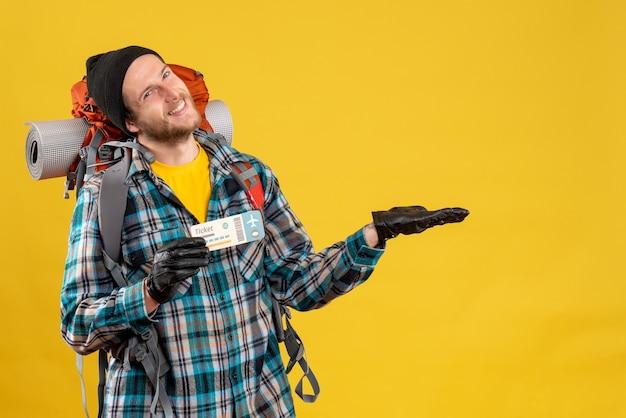 Vooraanzicht van blije jonge backpacker met het vliegticket van de zwarte hoedholding