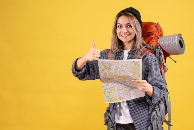 Vooraanzicht van blije reizigersvrouw met de kaart die van de rugzakholding duimen opgeeft
