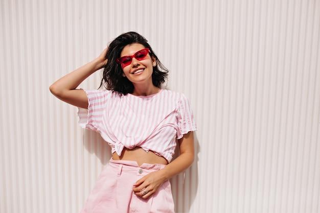 Vooraanzicht van blithesome vrouw in zomerkleding. winsome lachende vrouw in zonnebril staande op een gestructureerde witte achtergrond.
