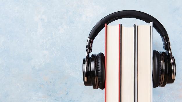 Vooraanzicht van boeken en oortelefoons met exemplaarruimte
