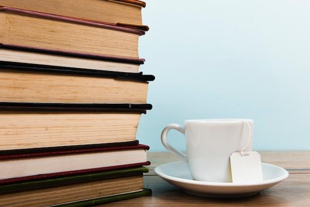 Vooraanzicht van boeken en theemok met exemplaarruimte