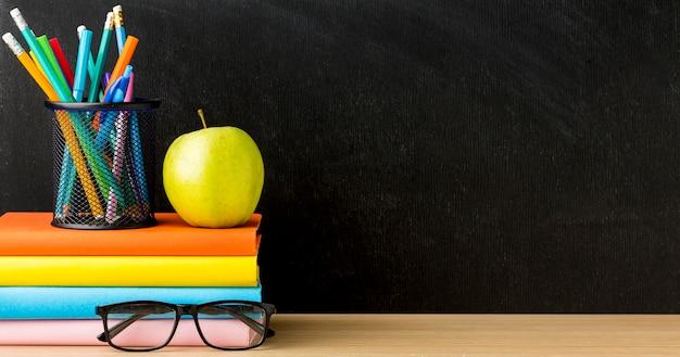 Vooraanzicht van boeken voor terug naar school met bril en kopie ruimte