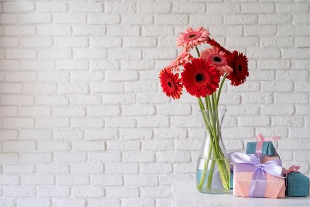 Vooraanzicht van boeket bloemen in vaas met geschenkdozen