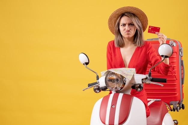 Vooraanzicht van boze jonge dame in rode jurk met creditcard in de buurt van bromfiets