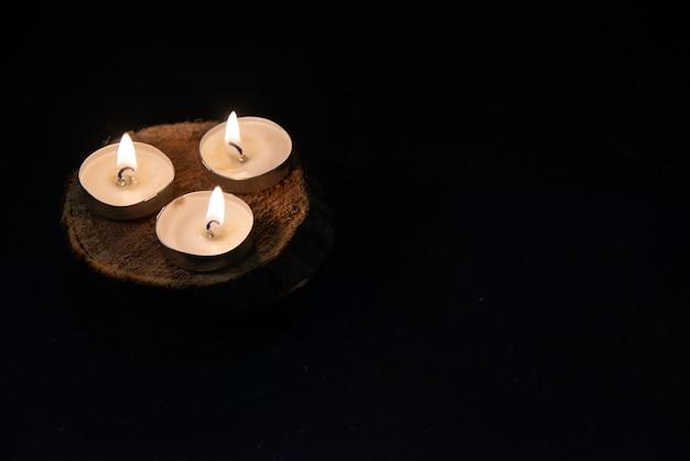 Vooraanzicht van brandende kaarsen op het pikzwarte oppervlak
