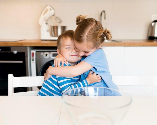 Vooraanzicht van broer en zus knuffelen
