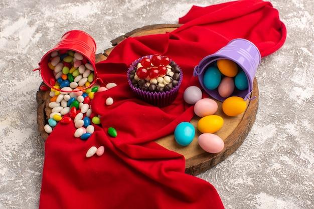 Vooraanzicht van brownie en snoepjes op het licht bureau