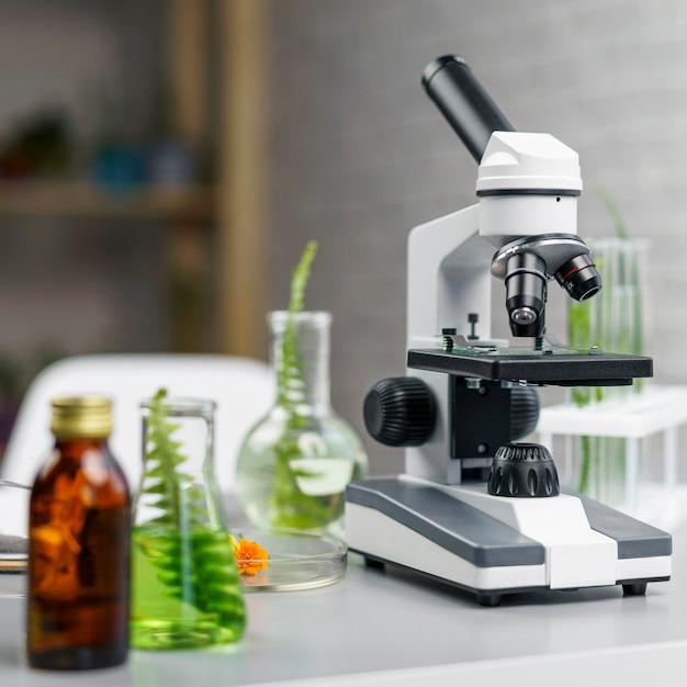 Vooraanzicht van bureau met microscoop en reageerbuizen