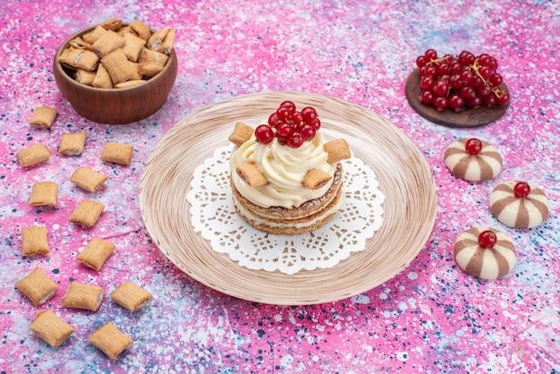 Vooraanzicht van cake met room samen met crackers en koekjes op het gekleurde oppervlak