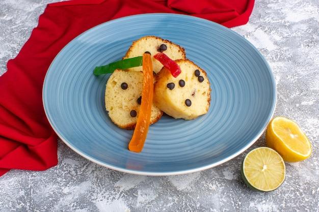 Vooraanzicht van cakeplak in blauwe plaat met chocospaanders en marmelade op rustiek grijs het koekjeszoete van de bureaucake bakken