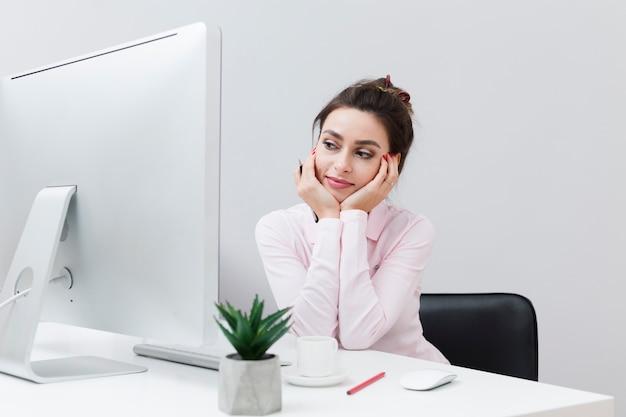 Vooraanzicht van charmante vrouw die bij bureau werkt en de computer bekijkt