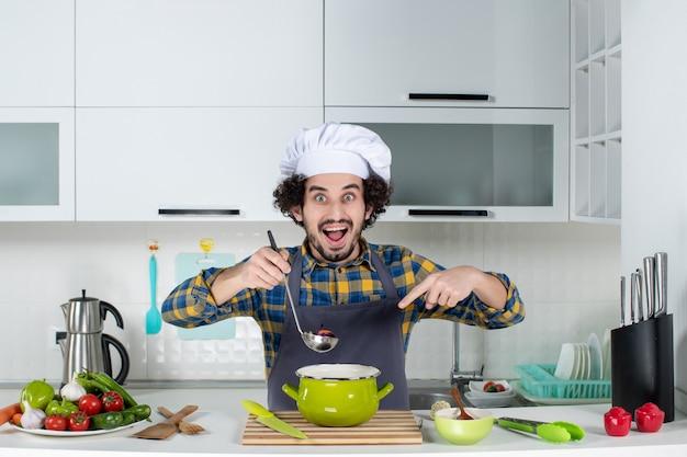 Vooraanzicht van chef-kok met verse groenten die proeven en kant-en-klaarmaaltijd in de witte keuken wijzen
